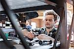 Focused mechanic examining car part in auto repair shop
