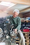 Mechanic rebuilding engine in auto repair shop