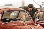Mechanics talking at classic car in auto repair shop