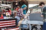 Mechanics fixing car engine in auto repair shop