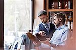 Businessmen examining dress shoes in menswear shop