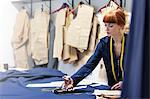 Female tailor cutting fabric in menswear workshop