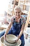Portrait smiling senior woman using pottery wheel in studio