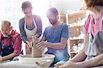 Teacher guiding mature man at pottery wheel in studio