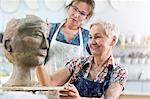 Teacher guiding senior woman sculpting clay face in pottery studio