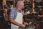 Portrait of shoemaker using laptop in workshop