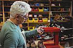 Shoemaker working with stretcher machine in workshop