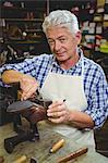 Portrait of shoemaker repairing a shoe in workshop
