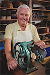 Portrait of shoemaker using sewing machine in workshop
