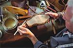 Shoemaker applying glue on shoe sole in workshop