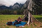 Hiker sitting by den using laptop, Yosemite, California, USA