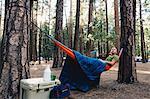 Hiker in hammock using laptop, Yosemite, California, USA
