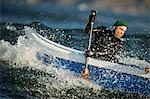 One man in a canoe in choppy ocean waves.