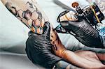 Artist wearing gloves tattooing design on human hand