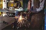 Mid-section of welder welding a metal in workshop