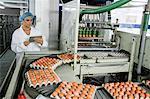 Female using digital tablet while examining eggs on conveyor belt in factory