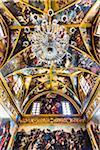 Crystal chandleir and elaborate paintings on the ceiling inside the Church of Santa Maria della Purita, Gallipoli, Puglia, Italy