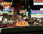 Taxi sign and neon lights at night on Nathan Road, Kowloon, Hong Kong, China, Asia