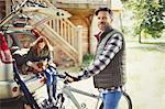 Portrait smiling man with mountain bike near car behind cabin