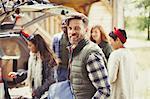 Portrait smiling man with friends unloading car