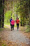 Three athletes jogging through forest