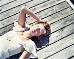 Woman lying on pier