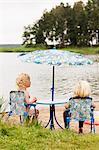 Little kids sitting on chair at beach