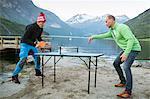 Men playing table tennis at lake