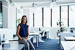 Confident mature businesswoman sitting on desk