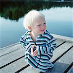 Boy in bathrobe sitting on jetty