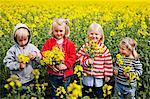 Children holding oilseed rape flowers
