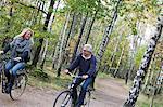 Senior couple cycling in forest, Delsjon, Gothenburg, Sweden