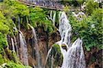 People on a footbridge crossing the large waterfall at Plitvice Lakes National Park in Lika-Senj county in Croatia