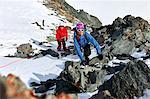 Mountaineer climbing up snow covered mountain, Saas Fee, Switzerland