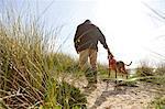 Man walking pet dog on sand dunes, Constantine Bay, Cornwall, UK