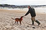 Man and dog on beach, Constantine Bay, Cornwall, UK