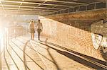 Young couple strolling under bridge on Regent's Canal, London, UK