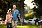 Smiling mature couple walking through a park.
