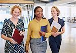 Smiling businesswomen walking in office