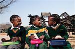 Three girls sitting on a wall eating their lunch, Meyerton Primary School, Meyerton, Gauteng