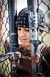 Teenage boy locked behind a wire fence.
