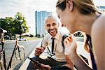 Germany, Berlin, Man and woman sitting on sidewalk