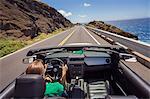 USA, Hawaii, Oahu, Banzai Pipeline, Rear view of mid adult woman driving convertible car