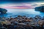Spain, Majorca, Palma de Mallorca, Rocky coastline with sea at sunrise