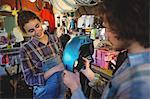 Mechanics examining a bicycle helmet in bicycle workshop