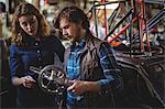 Mechanics repairing bicycle in workshop