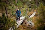 Female hiker running on footbridge over trees during autumn