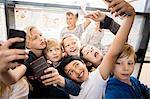 Group of boys taking selfie in corridor