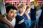 Portrait of happy boys standing in school corridor