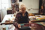 Craftswoman using digital tablet in workshop